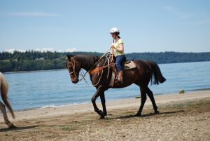 Camper horseback riding on the beach at Camp Sealth