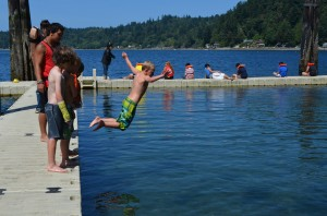 boy jumping off of dock
