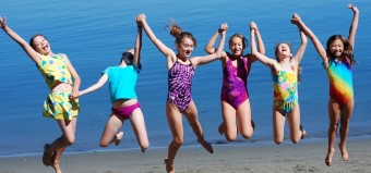 girls jumping on beach