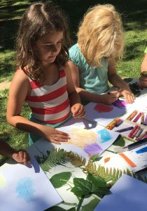 Campers using crayons to create leaf rubbing art.