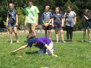 Campers helping their blindfolded teammate find puzzle pieces.