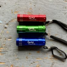 Red, green, blue Camp Sealth flashlight with black wrist strap