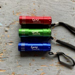 Red, green, blue Camp Sealth flashlight with black wrist strap