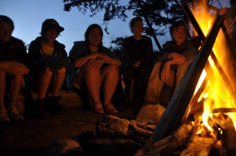 Campers sitting at a campfire