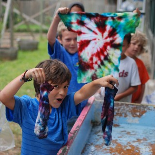 Campers showing tie dye projects