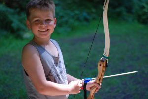 Smiling camper at archery