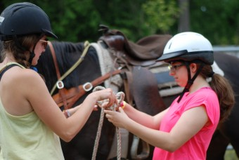 Counselor helping a camper with horse