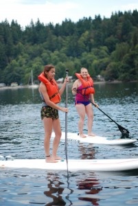 Campers standing on paddle boards