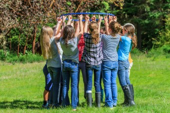Students teambuilding with helium hoop at Camp Sealth